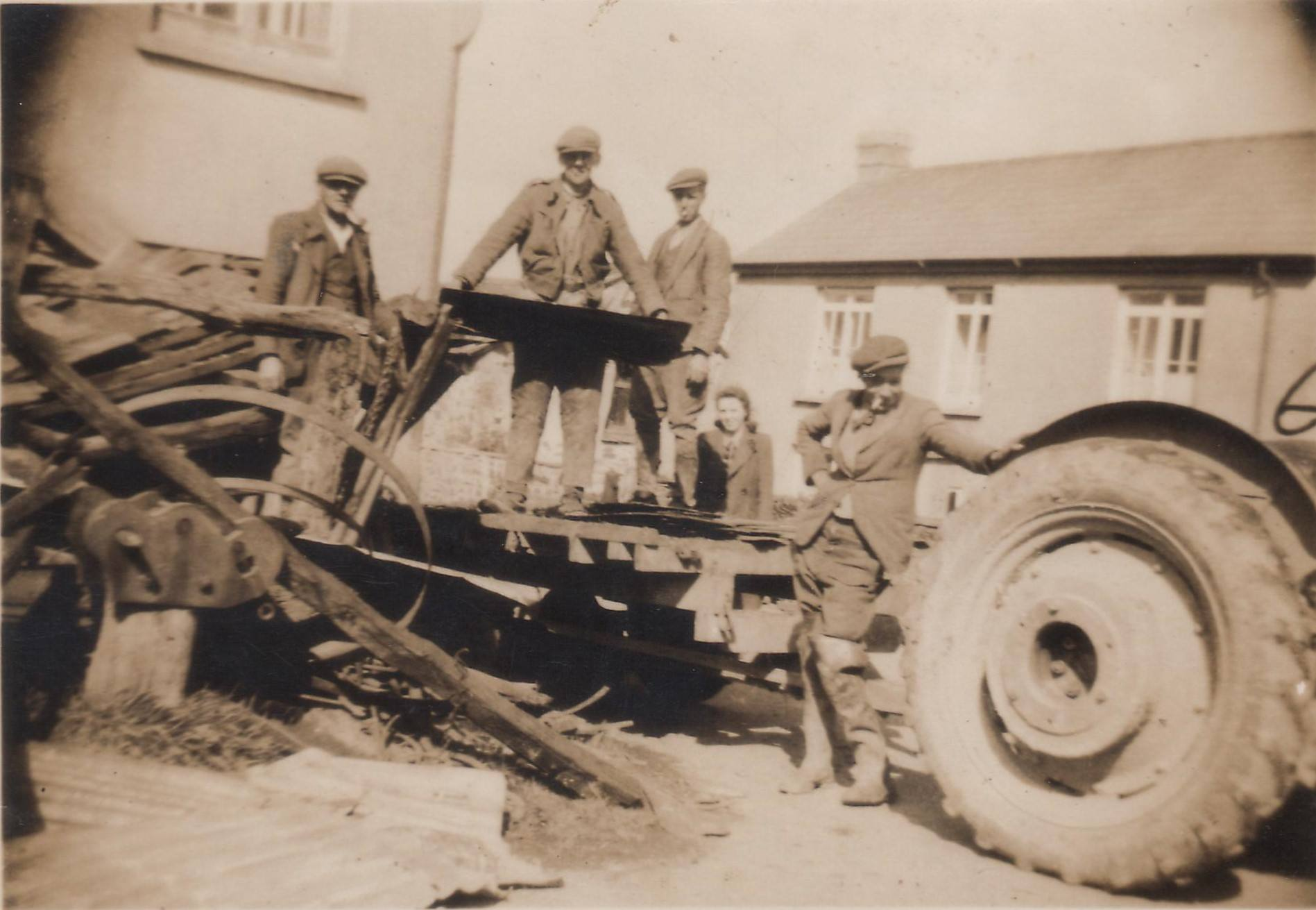 Clearing up W. Lakeman's Blacksmithy after its collapse Bill Tippett (by tractor) Walter Hicks & Bill & Frank Wickett. Photo courtesy of Gary Lashbrook.