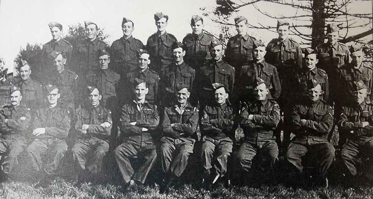 Back row ?, Ronald Prout, Ken Prout, ?, Stan Jones, ?, ?, ?, Middle row Alan Jenkin, Horace Gillbard, Farmer Harris,?, ?,?, Douglas Frayne, Albert Pyke, Albert Cross. Front row Stan Reed, Bob Moffatt, ?, Willis, Harry Gould, Titball, John Grylls, Arthur Francis, Percy Wren. The stores for the Homeguard were situated in a nissen hut at the end of the top lane at Hole Barton.