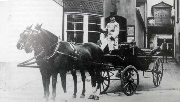 The White Hart Coach with its driver Mr. Uren leaving the Hotel's stables and coach house, now the White Hart Arcade