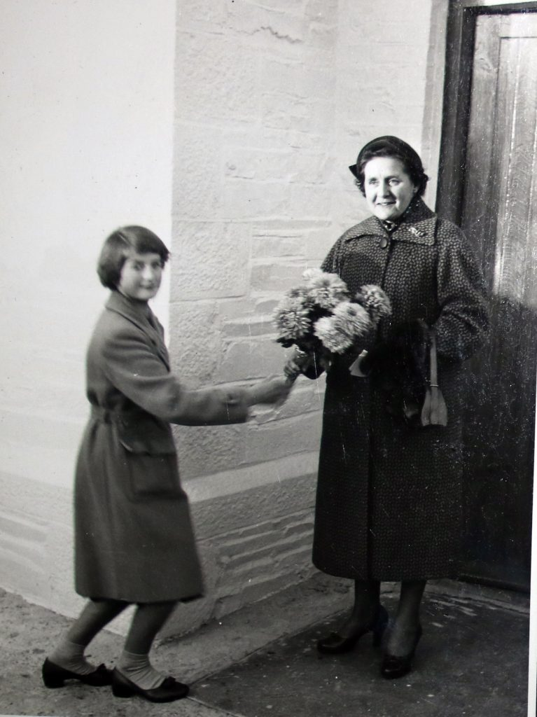 Gwendoline Robins is presented with a bouquet at the 1955 reopening of Laneast Chapel