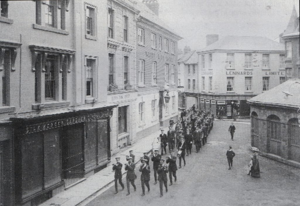 Launceston Town Band lead up a procession through the Square c.1920.